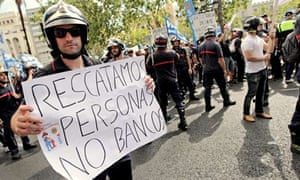 Firefighter's signs reads 'We rescue people, not banks', during a demonstration in Valencia