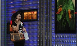 A woman leaves a luxury shopping mall in Shanghai