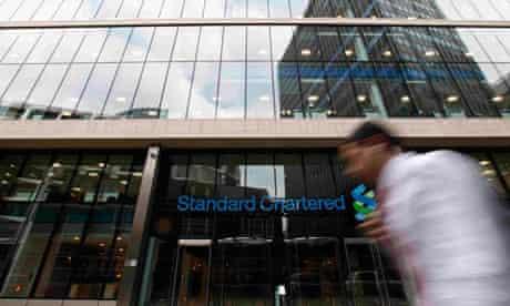 Man walking past a Standard Chartered bank in London