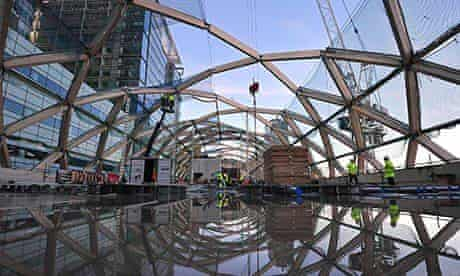 Builders work on a roof above the Canary Wharf Crossrail station