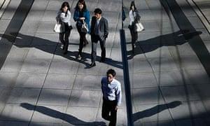 Office workers walk on a street in Tokyo