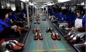 Employees work at a shoe factory in Lishui, Zhejiang province, China