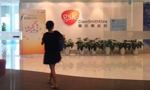 A Chinese employee walks into a GlaxoSmithKline (GSK) office in Beijing