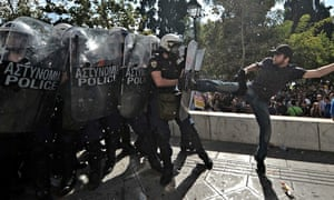 A demonstrator clashes with riot police during a strike in Athens, Greece, 2012