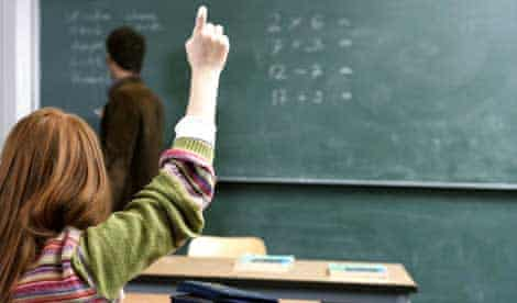 A girl pupil raises her hand in a classroom