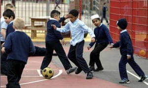 Children playing football in the playground at Deepdale junior and infant school in Preston