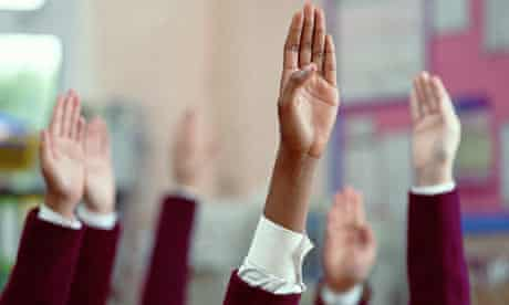 School children raise their hands to answer a question in a classroom