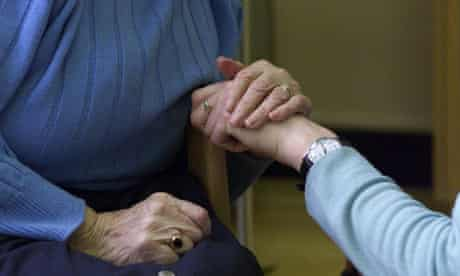 Careworker holding the hand of an elderly woman at Sotheby's Mews day centre
