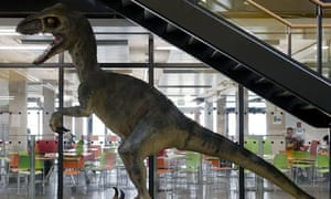 A large model dinosaur sits in the hallway of Langley academy