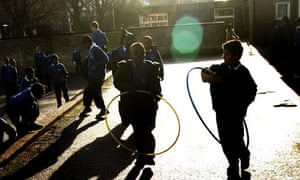Children playing with hula-hoops at school