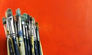 Used paintbrushes on an orange background