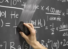 Hand erasing maths equations on classroom blackboard
