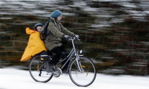 A woman and child cycle through snow