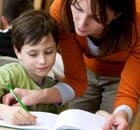 Teacher helps pupil with his work