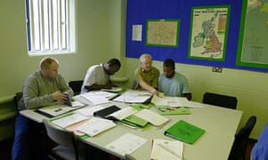 Inmates work with a tutor in a prison education department