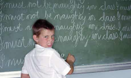 Schoolboy writing lines on blackboard