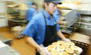 Wilsen Lau, 19, prepares burgers at the McDonalds restaurant in Kingsford, Sydney