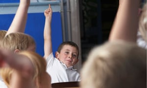 Boy putting up hand in class