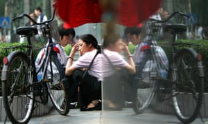 A Chinese student and her mother wait outside a school during national college entrance exams