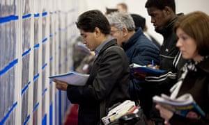 Jobseekers search for employment opportunities at a graduate recruitment fair