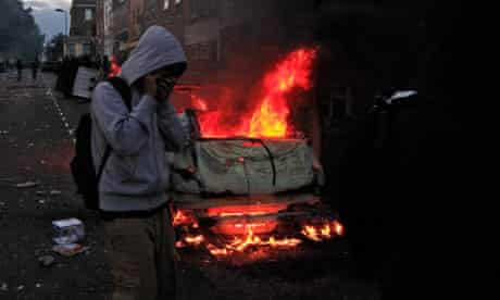 young people walk past burning car in Hackney riots