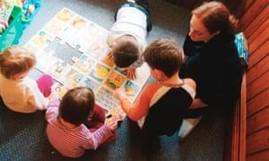 Trainee nursery worker with small children in nursery UK
