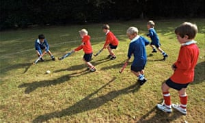 Schoolchildren playing hockey during their sports lesson in the school playing fields