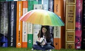 Teenage girl reading with giant books
