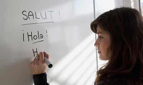 woman writing hola on a board