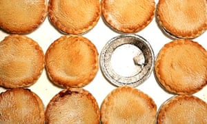 MInce pies surrounding an empty foil container for an already eaten mince pie