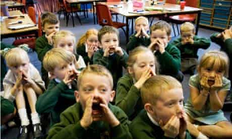 Primary children learning with a Jolly Phonics reading scheme.