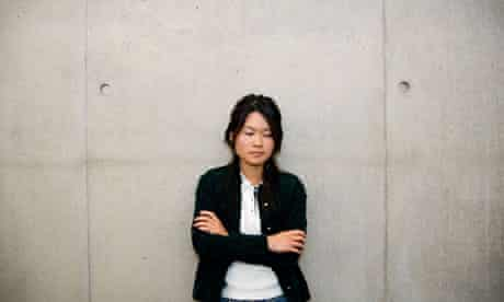 A single asian woman standing against cement wall.