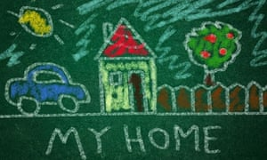 Child drawing of home on a green chalkboard