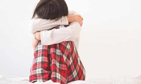 Sad woman wearing pyjamas sitting on bed