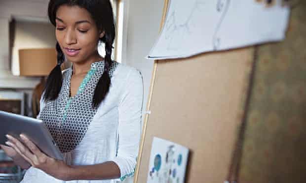 Female jewelry designer using digital tablet at workshop