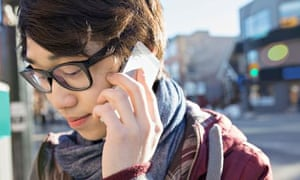 Young man student talking on smart phone outdoors