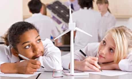 School girls writing report on wind turbines in classroom