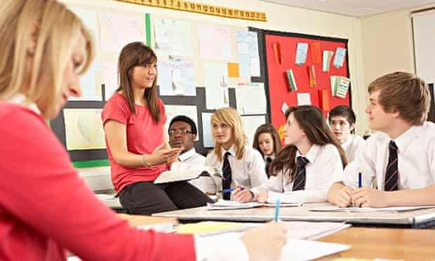 Teenage Students Studying In Classroom With Teaching assistant