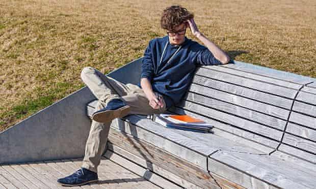 Teenage boy sitting on bench