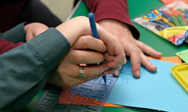 teacher helping special needs child