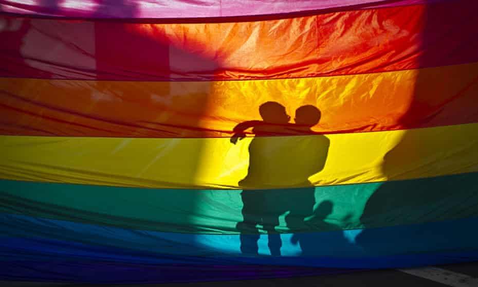 Men embrace behind a rainbow flag.