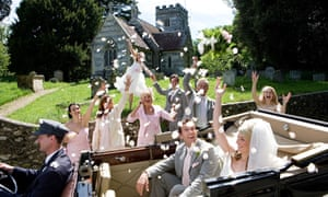 Wedding party throwing confetti on bride and groom in convertible vintage car by church, smiling
