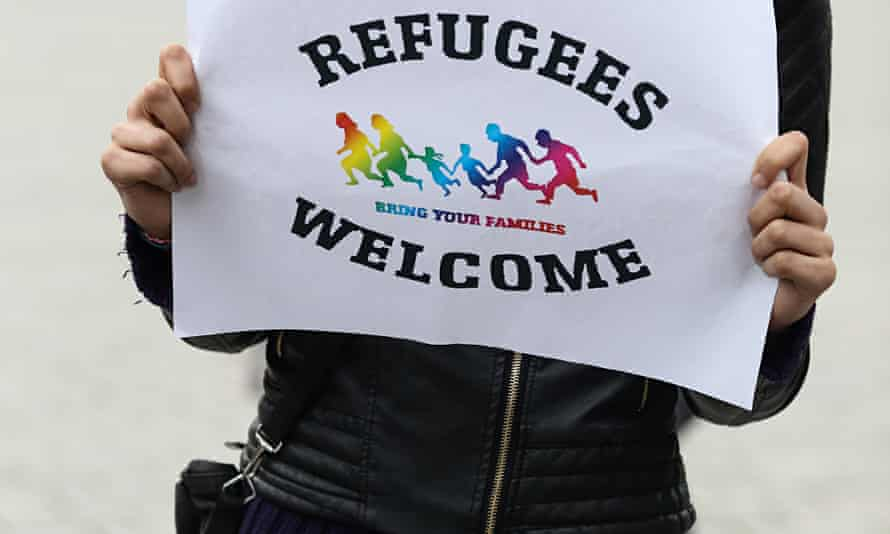 A woman in German holds up a 'refugees welcome' sign