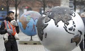 COP15 : A man carrying a baby walks past a globe in downtown Copenhagen