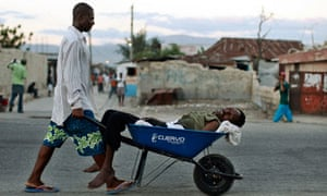 A Haitian with symptoms of cholera is transported in a wheelbarrow in Port-au-Prince, Haiti