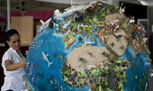 COP16 Cancun : A woman looks at a globe model in the climate village