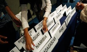 Cancun COP16 : A woman hands out names of countries to participants