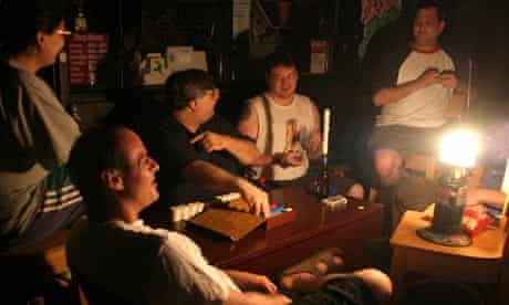 Men playing cards with candles during power blackout