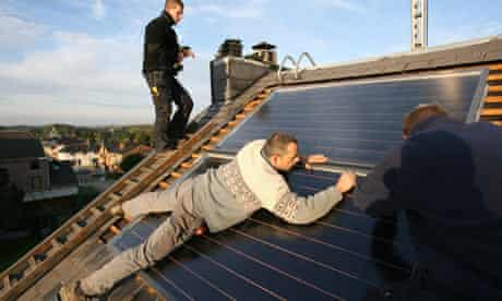 Technicians install a solar panel for hot water on the roof of a house