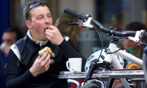 A cyclist enjoys a coffee and snack at an outdoor cafe in Bath